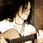 Close up of Katrina Curtiss playing her guitar