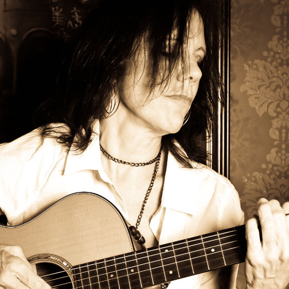 Close up of Katrina Curtiss playing her guitar